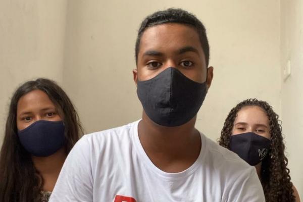 três adolescentes, duas meninas e um menino, posam de máscara.