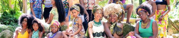 Quinze jovens mulheres posam em uma área aberta e arborizada. Elas usam vestidos e saias estampadas