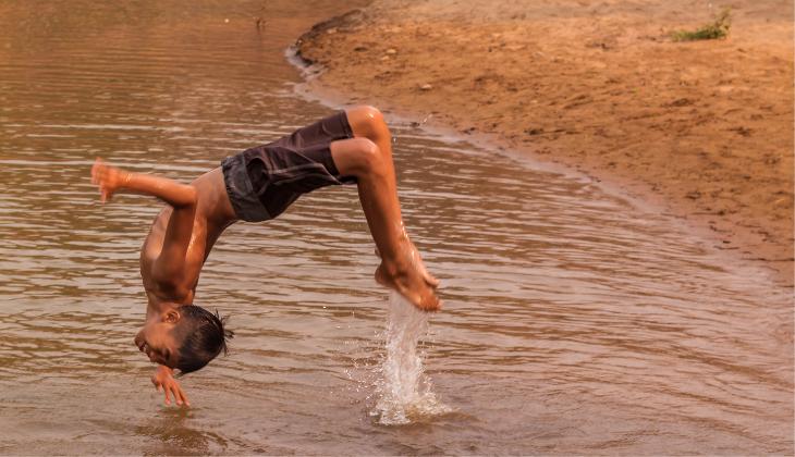 Foto de um adolescente indígena fazendo uma acrobacia ao pular em um rio. Ele sorri e está usando uma bermuda.