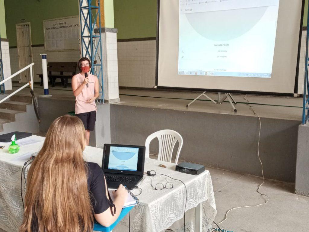 Foto de um jovem falando a frente de um telão. Na sua frente, há uma jovem sentada de costas.
