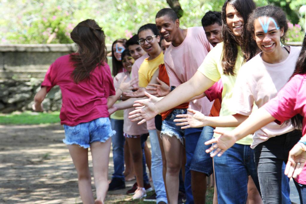 Foto de adolescentes brincando. Eles sorriem enquanto uma jovem corre na frente deles.