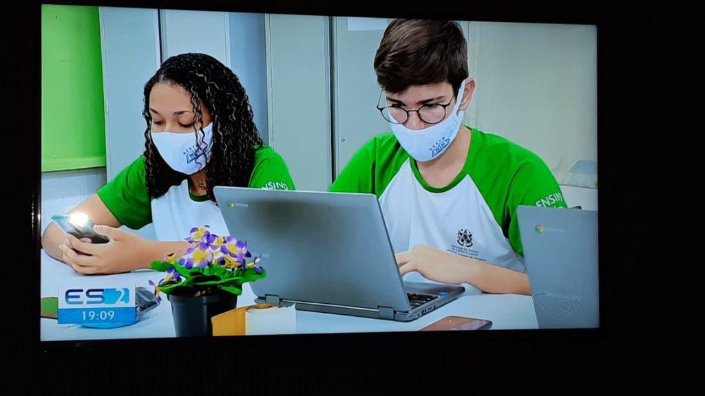 Foto de uma tela com uma jovem negra e um jovem branco usando máscaras de proteção e mexendo no computador. Eles vestem o uniforme da escola que é verde e branco.