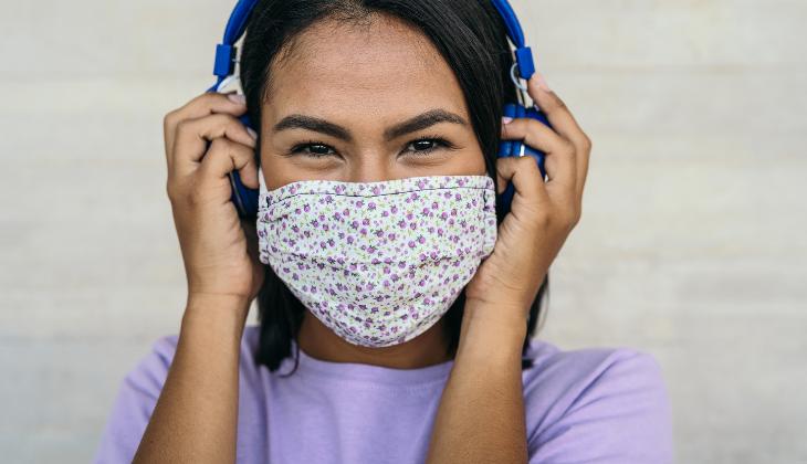 Foto de uma jovem ouvindo música com fone. Ela usa máscara e está sorrindo.