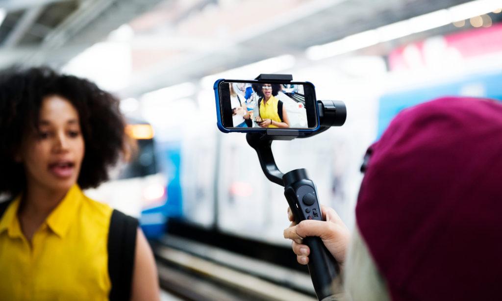 Foto de uma pessoa branca segurando um celular que filma uma mulher negra