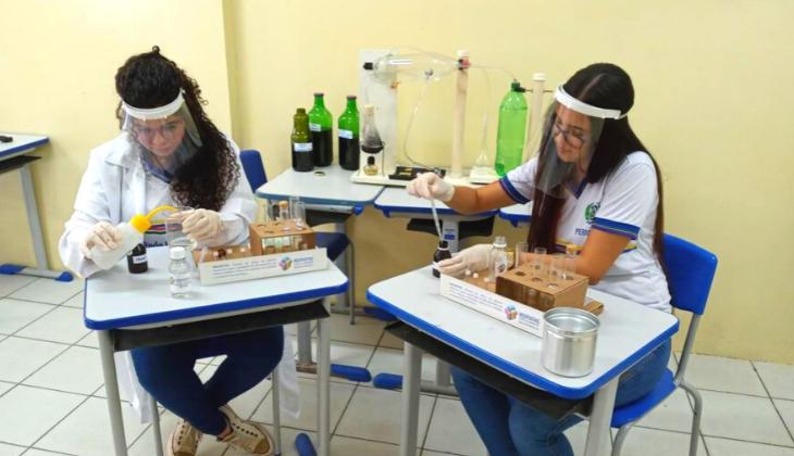 Duas adolescentes - negra e branca - testam produtos com materiais de laboratório químico. Ambas usam protetor facial e estão de uniforme.