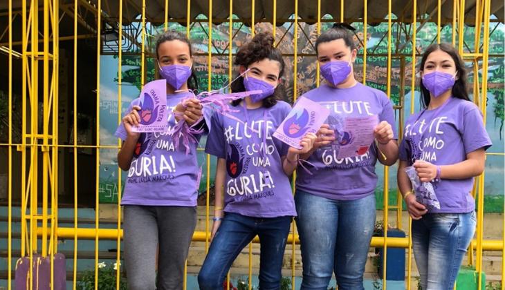 Foto de quatro meninas: uma negra e três brancas. Elas vestem máscara roxa e uma camiseta roxa com os dizeres: Lute como uma guria. Todas seguram papéis roxos com o desenho de uma chama violeta