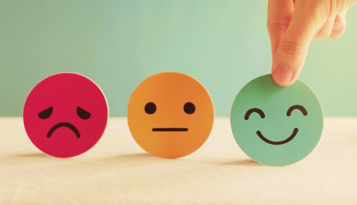 Foto de três carinhas de papel: uma vermelha e triste, outra amarela e apática, e uma verde e feliz. Há uma mão branca segurando a última carinha.