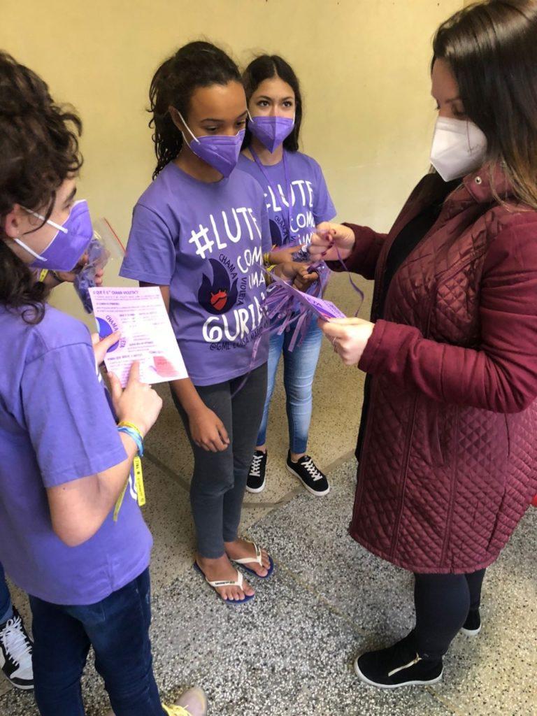 Foto de três meninas vestindo camisetas roxas com os dizeres: Lute Como uma Guria. Elas conversam com uma mulher. Todas usam máscara de proteção e seguram fitas roxas e um folheto.