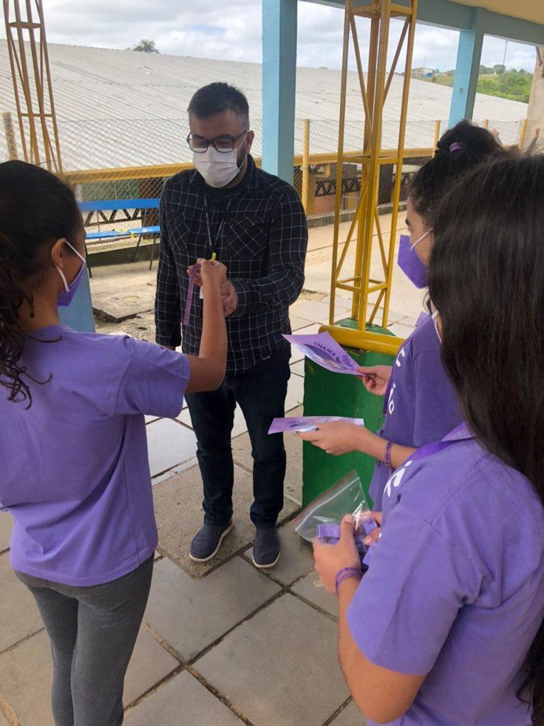 Foto de três meninas que vestem camisetas roxas e distribuem fitas roxas e folhetos sobre educação sexual.