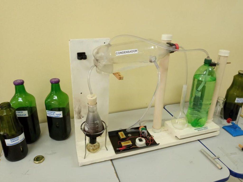 Foto de um destilador feito com garrafa PE. Em volta, há garrafas com líquidos.