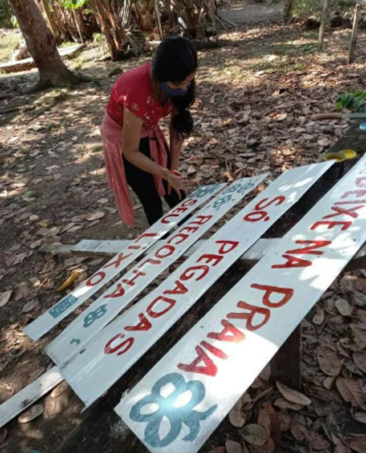 Foto de uma adolescente escrevendo com tinta em uma placa de madeira.