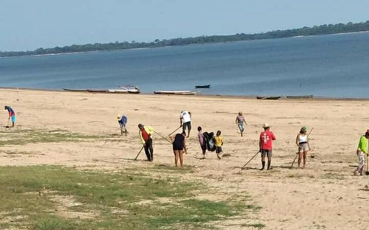 Foto de pessoas fazendo a limpeza da margem de um rio.