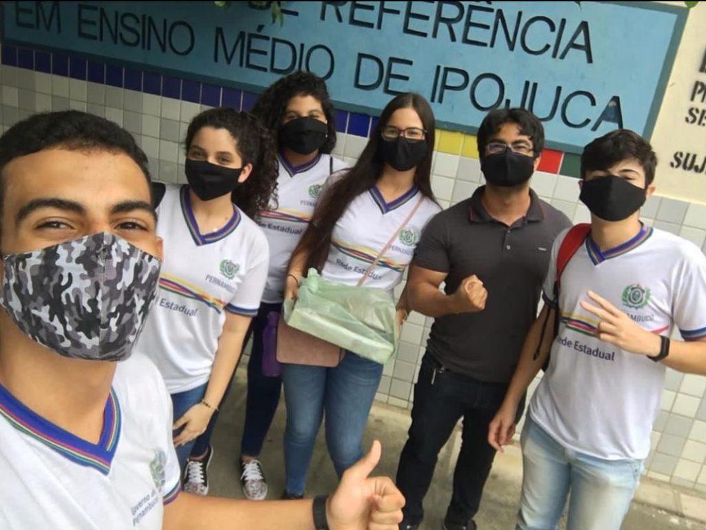 Foto de seis pessoas posando para uma selfie: 5 jovens usando uniforme e um adulto. Todos usam máscara facial.