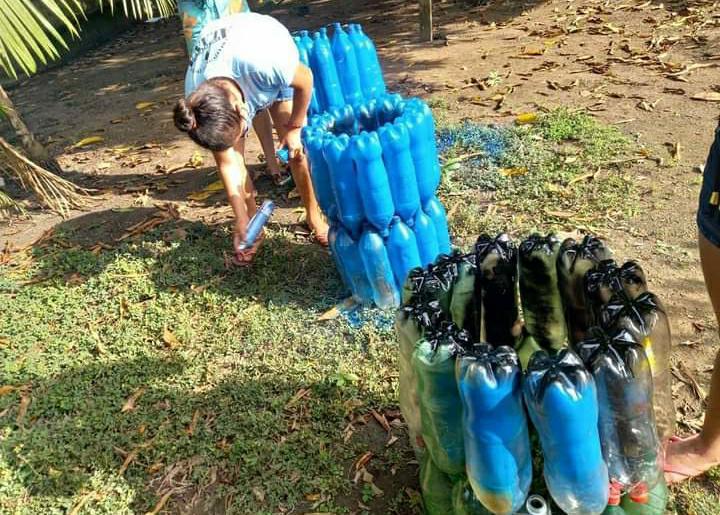 Foto de uma jovem pintando lixeiras feitas de garrafa pet em um gramado.