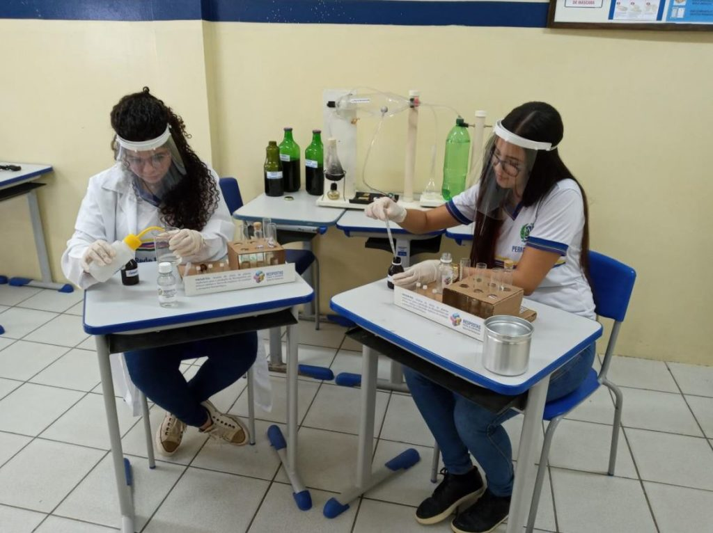 Foto de duas adolescentes testando produtos com materiais de laboratório químico. Ambas usam protetor facial e estão de uniforme.