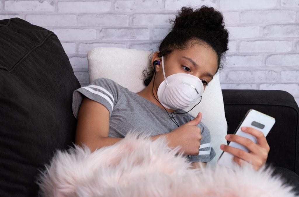 Foto de uma adolescente negra em uma chamada de vídeo pelo celular. Ela usa máscara de proteção e faz sinal de joinha para o celular deitada em um sofá.