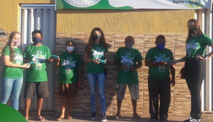 Foto de adultos e crianças usando mascaras e camisetas verdes em uma rua ensolarada.