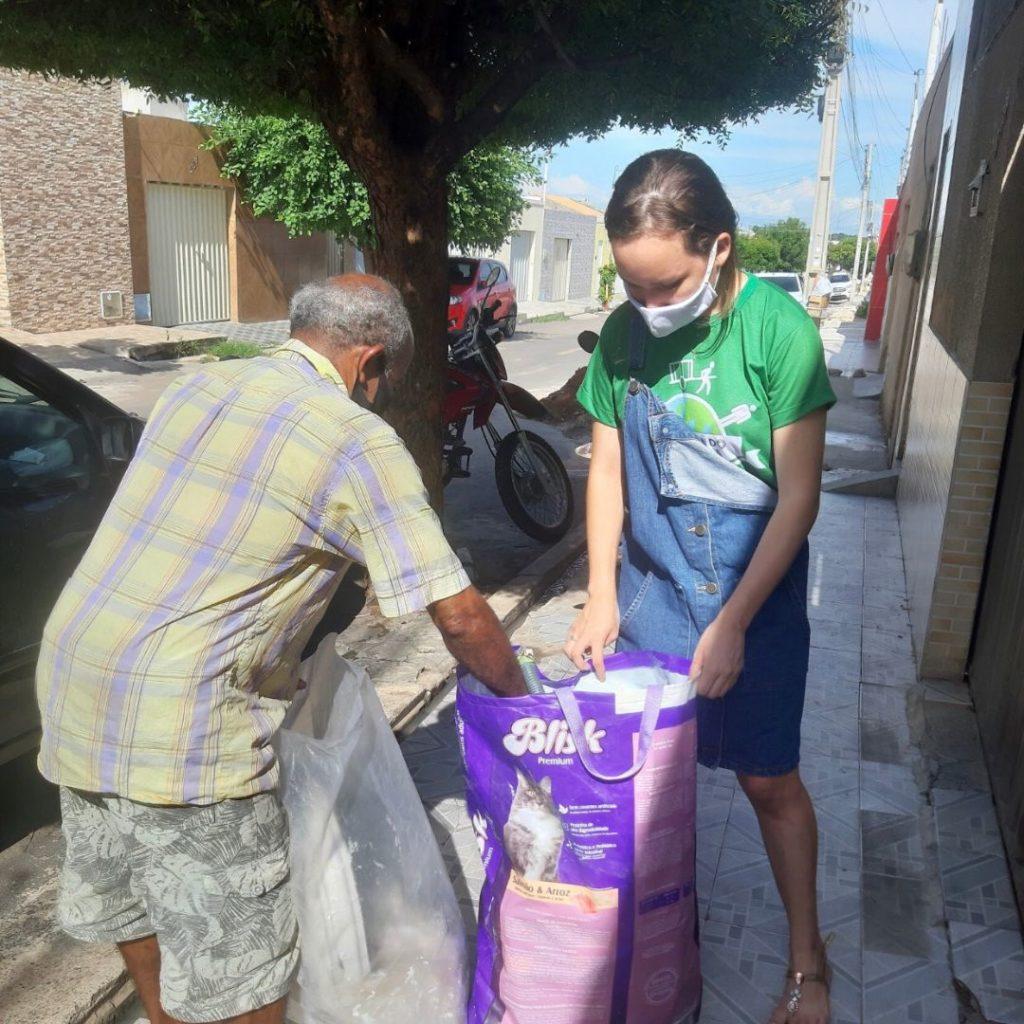 Foto de uma adolescente branca segurando um saco de lixo reciclável para que um homem idoso pegue materiais.